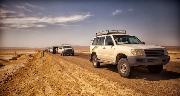 사하라 사막에서 사파리와 아프리카 여행 - 극한의 모험. 염습지, 황량한 도로 및 오프로드 차량 한가운데의 뜨거운 태양에서 지프 고장.
