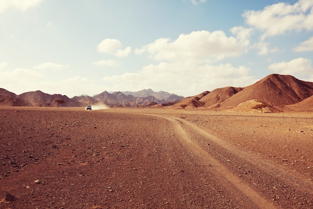 Safari and extreme travel in africa. drought  mountain landscape with dust off road in offroad car expedition.