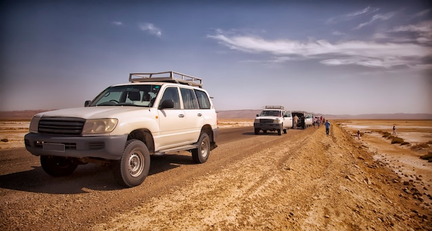 Safari and travel to africa-extreme adventures in sahara desert. jeep breakdown in scorching sun in middle of salt marsh, deserted road and off-road vehicles