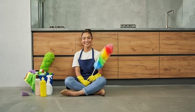 安全で清潔。洗剤でアパートを掃除した後、休んでいる間、カメラに微笑んで、掃除ダスターを持っているうれしそうな若い女性。家事とハウスキーピング、クリーニングサービスのコンセプト