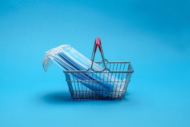 Безопасные и онлайн-покупки по концепции карантина. корзина для покупок с защитной медицинской маской поверх
