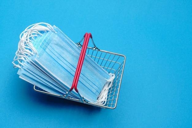 検疫の概念に関する安全でオンラインショッピング。保護医療マスク付きの買い物かご