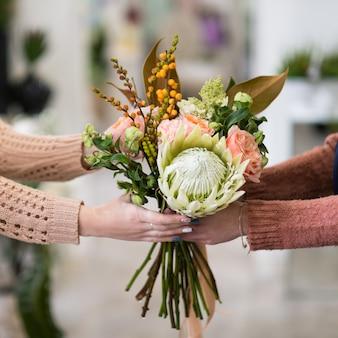 あなたが愛する人のための安全で迅速なフラワーブーケの配達。バラのダリアとベリーの創造的な配置を保持している女性の手