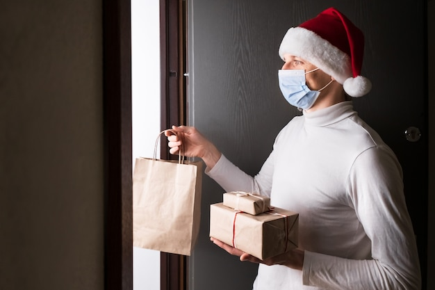 Безопасная доставка на рождество и новый год, человек-курьер в красной шляпе санта-клауса и защитной маске во время карантина от коронавируса. подарки и дом