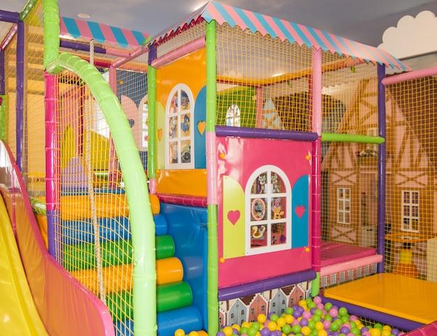 屋内の遊び場にある家の形をしたネットとカラフルなボールを備えた安全なカラフルな子供用トランポリン。