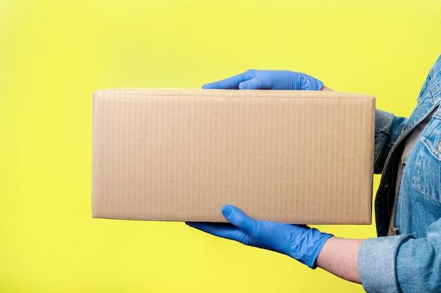Безопасная доставка. руки женщины конца-вверх в перчатках с картонной коробкой. анти-коронавирусная концепция. макет.