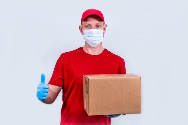 安全な配達。赤い制服と保護医療マスクと手袋の宅配便は、段ボール箱を保持し、非接触で注文を配送します。ボランティアの寄付。