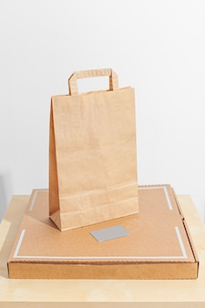 Safe delivery of food in a craft bag and pizza delivery man at home on a white background