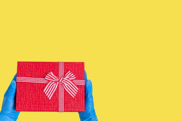 Safe delivery of gifts concept. hands in blue gloves hold a red gift box with a bow