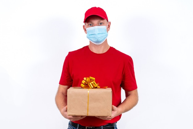 Safe delivery of gifts for holidays. a courier in red uniform and protective medical mask holds box with a bow.
