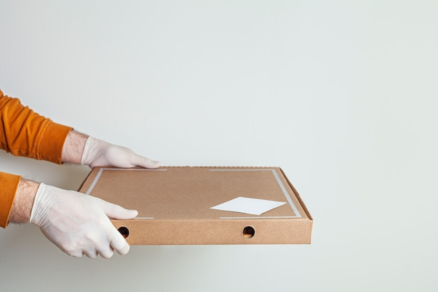 白い背景の上の自宅でクラフトバッグとピザの配達人の食品の安全な配達