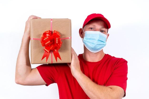 休日の贈り物の安全な配達。赤いユニフォームと保護医療マスクの宅配便は箱を保持します
