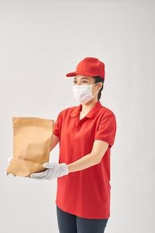 赤いドレス、フェイスマスク、手袋を手に紙袋に入れて安全な配達の女性