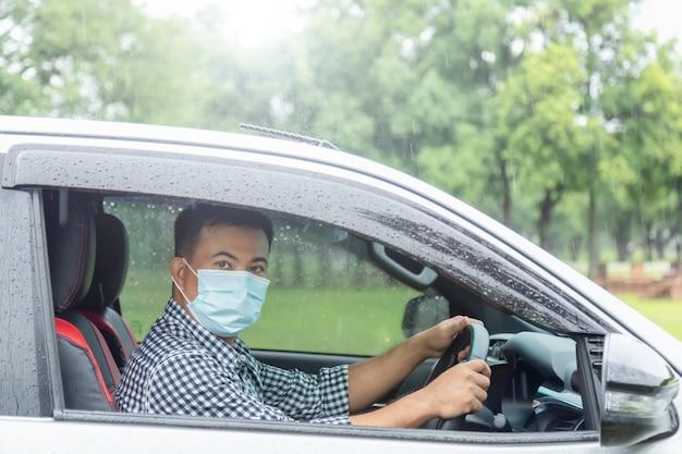 비가 오는 날에 안전한 운전. 마스크를 쓰고 비가 내리는 동안 운전하는 아시아 사람들. 렌즈 플레어 효과