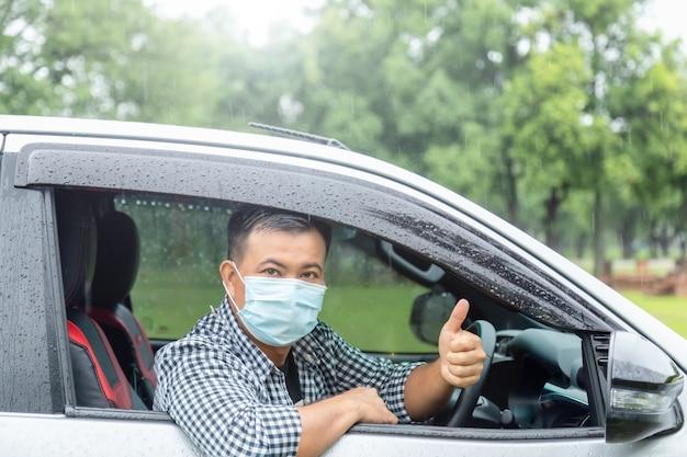 Безопасное вождение в дождливый день. азиатский человек в маске сидит в машине и показывает палец вверх. эффект бликов линз