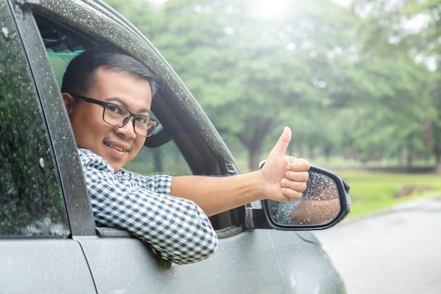 Безопасное вождение в дождливый день. улыбаются люди, сидящие в машине, и пальцы вверх. концепция счастливого вождения