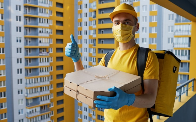 Safe food delivery. courier in yellow uniform, protective mask and gloves delivers takeaway food during coronovirus quarantine