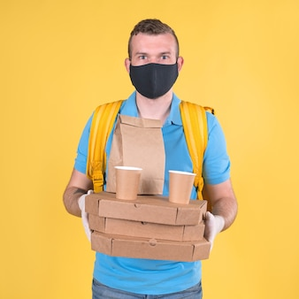 Безопасная доставка еды. небритый кавказский молодой блондин доставщик еды в синей форме торговой марки