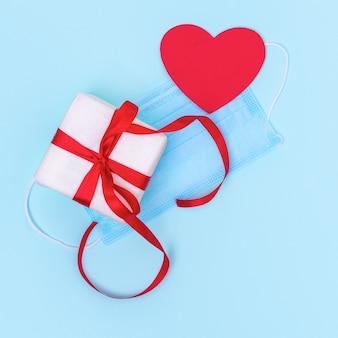 안전한 선물 개념. 빨간 리본 및 빨간 종이 선물 상자 파란색 보호 마스크에 마음을 사랑