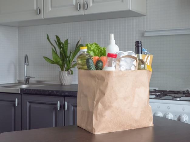 安全な宅配。モダンなキッチンでの牛乳、卵、野菜、ワインなどのパッケージ
