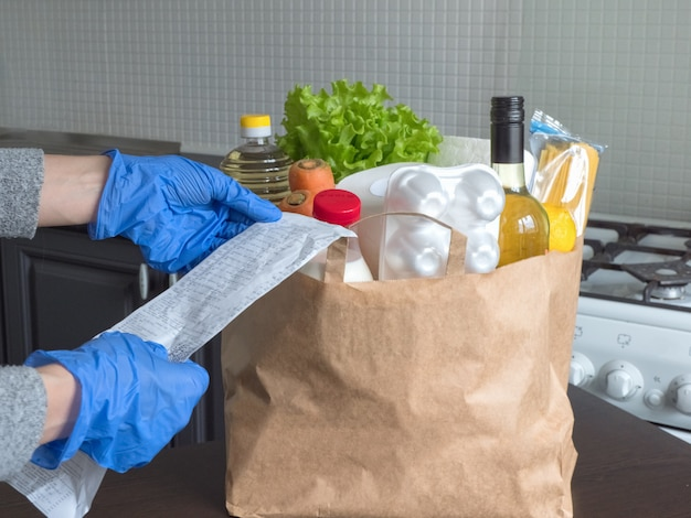 Safe home delivery, check verification. a package with products such as milk, eggs, vegetables and wine in a modern kitchen