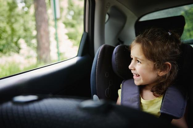 車内でのお子様の安全な移動。愛らしい女の赤ちゃんは車での旅行を楽しんで、安全ブースターのチャイルドシートに座っている間、開いた窓の外を見る
