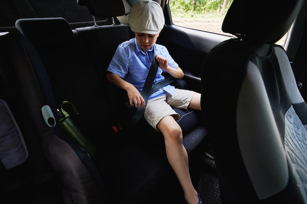 車内でのお子様の安全な移動。愛らしい男の子が車内のチャイルドシートのシートベルトを締めます。子供の安全輸送の概念