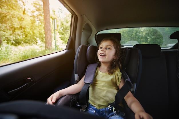 車内でのお子様の安全な移動。車で旅行中にシートベルトを着用したチャイルドシートの幸せな女の子