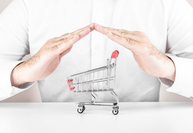Safe online shopping concept. shopping cart protected with hand on white