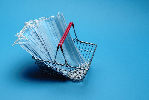 Safe and online shopping on quarantine concept. shopping basket with protective medical mask over blue background