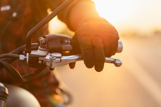 安全な乗り心地のコンセプト。クラッチにライディンググローブを着用したモーターサイクリストのマクロ左手。コピースペースのある道路での屋外撮影