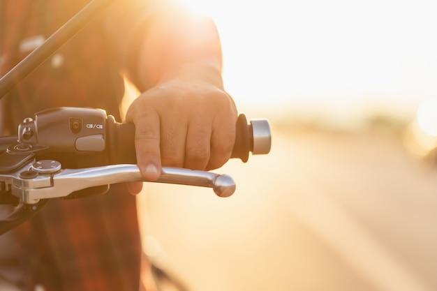 安全な乗り心地のコンセプト。クラッチに手袋のないモーターサイクリストのマクロ左手。コピースペースのある道路での屋外撮影