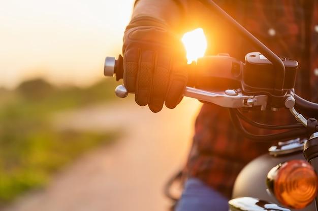 安全な乗り心地のコンセプト。ハンドブレーキにライディンググローブを着用したモーターサイクリストのマクロ右手。コピースペースのある道路での屋外撮影