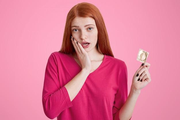 安全なセックスの概念。赤い長い髪とそばかすのある魅力的な若い女性がコンドームを手に保持