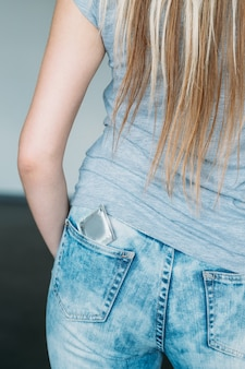Safe sex. condom as a pregnancy prevention. female backview with a contraceptive in her jeans pocket