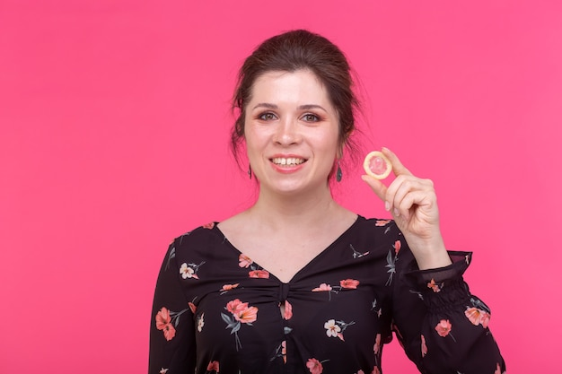 Safe sex, health and contraception concept - woman holding in hands a condom on pink wall