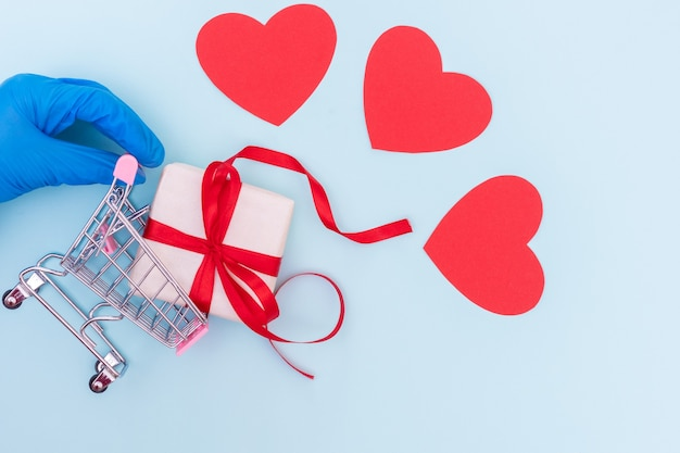 Safe shopping concept. hand in a blue medical glove holds a shopping trolley with a gift box
