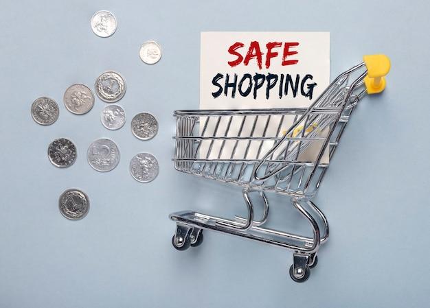 安全な買い物の碑文。コイン付きの金属製カート。