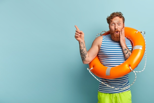 Safe sinking concept. astonished red haired man holds orange lifebuoy, maintains safety