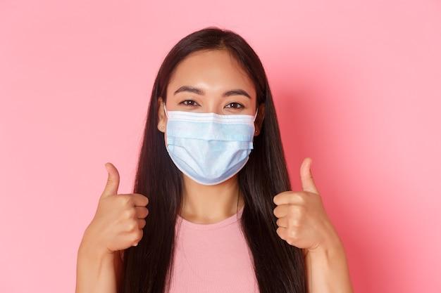 安全な観光、コロナウイルスのパンデミック中の旅行とウイルスの概念の防止。彼女の休暇のように親指を現して医療マスクで満足している、陽気なアジアの女の子の観光客のクローズアップ