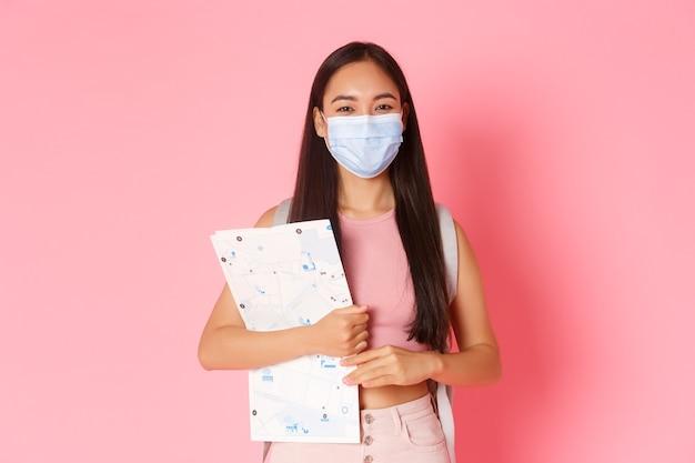 安全な観光、コロナウイルスのパンデミック中の旅行とウイルスの概念の防止。かわいいアジアの女の子は、海外旅行、旅行中に社会的距離を離れて行く地図と医療マスクの観光。