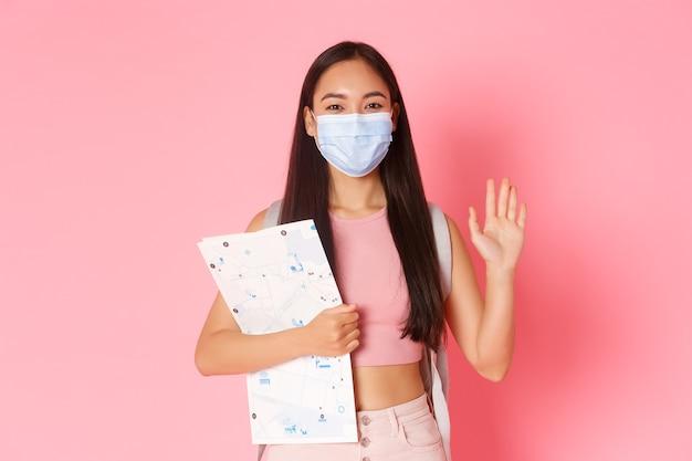 安全な観光、コロナウイルスのパンデミック中の旅行とウイルスの概念の防止。地図とbacpackが海外に行く、手を振ってこんにちは、医療マスクを着用するフレンドリーなかわいいアジアの女の子の観光客