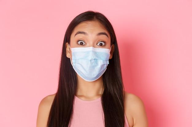 安全な観光、コロナウイルスのパンデミック中の旅行、ウイルスの概念の防止。医療マスクで驚いて驚いたアジアの女の子の観光客のクローズアップは眉を上げ、驚いているように見えます。