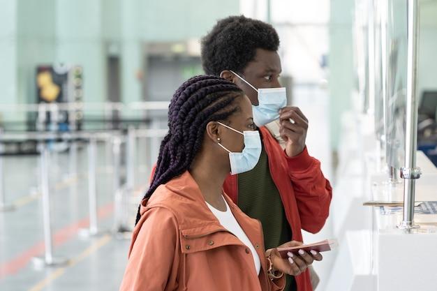空港チェックイン時にマスクで黒人カップルのコロナウイルス発生クローズアップで安全な旅行と観光