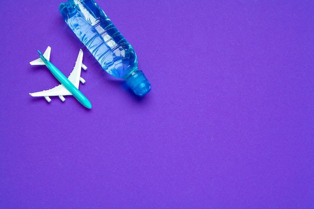 Safe travel . clear water bottle and toy plane.