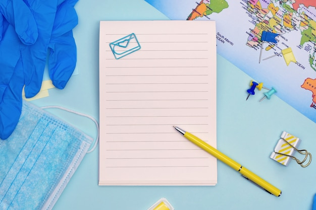 Safe travel planning. medical mask, gloves, stationary items and map on blue background with copy space.