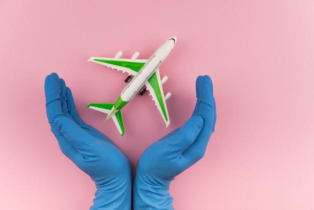 안전한 여행 개념. 의료 장갑에 손에 비행기. 격리 및 폐쇄 중 안전 비행 및 여행.