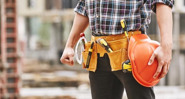 安全赤を保持している建設ツールと男性のプロのビルダーの安全な作業トリミング写真