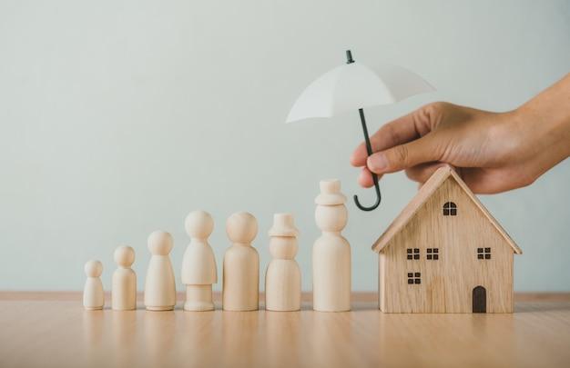 木製の人形、家族、家に傘を保持している手。家族介護の概念家族safethandsは、木製の人形、家族、家に傘を差します。