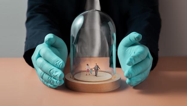 コロナウイルスコンセプト中の安全衛生保険。ガラスのドームカバーの中を歩く家族のミニチュアフィギュア